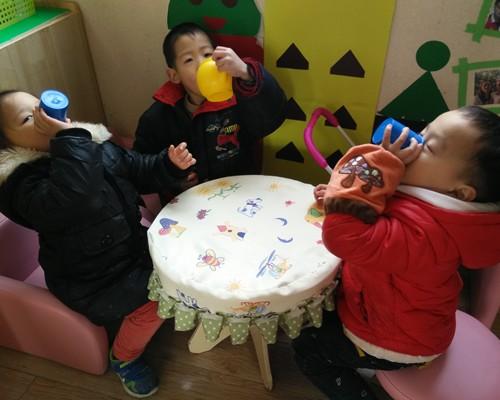 有的幼儿坐在沙发上喝茶,有的坐在梳妆台前给娃娃穿衣服,有的在用微波