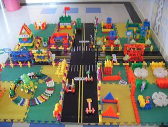 """本次幼儿建构大赛分小、中、大班三个年龄段,分别以""""动物园""""、""""马路上""""、""""上小学""""为主题内容,共有百余名幼儿参加了比赛。比赛运用了雪花积木、软胶粒、塑料插塑等幼儿园常用积木进行主题建构,同时教师根据幼儿的不同年龄提供了相应的辅助材料。此次建构大赛的成功开展,不仅促进了幼儿的动手能力及创造性思维的发展,还提升了幼儿游戏水平,进一步推动了建构游戏在幼儿园的深入开展。"""