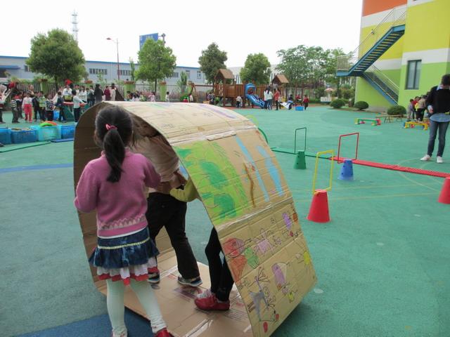 """上午八点,朱行幼儿园的操场上已经人头攒动,深受孩子们最喜爱的大班混班区域活动即将开始。整个运动场地在大班组老师的精心布置下分成钻爬区、球类区、木制器械区、跳跃区、沙水区等五个区十项运动内容。在每项运动内容的设置上,老师们也充分考虑了情境性、趣味性和挑战性。如木制器械区创设了""""城堡着火了""""的场景,逃生队的成员通过钻爬等方式有序地从安全出口逃离火场,救援队的成员从不同的路线抬着担架救出城堡中的""""小动物"""",有的成员还拿来了""""灭火器""""勇敢地冲"""