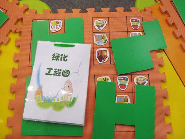 """游戏材料  游戏场景 游戏适合年龄:4~6岁 游戏对象:幼儿独立参与(或亲子共同参与) 游戏目的:鼓励幼儿为每一张工程图盖上一块""""护绿草坪"""",使其符合构图要求,增强幼儿的空间意识。 主要材料:大号泡沫软垫若干块(垫上标有四组相同规格的九格图形),裁成不同形状的绿色KT板若干,护绿工程图,各种房子的图片。 游戏玩法: 游戏前,成人先在一块大垫子上的四组九格图形中,按照一定的顺序和模式将各种不同房子的图片固定在小方格内。幼儿扮演世博园艺师,翻开工程图并仔细阅读,按照工程图上的说明,完"""