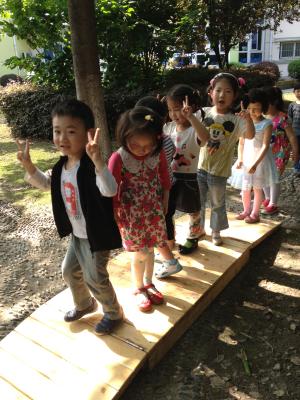 幼儿园的小树林里架了一座小木桥,看,我们在学小动物过小桥哦!