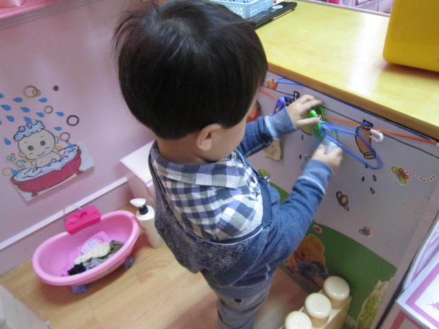 娃娃家的主题活动,孩子们自己做相框,给妈妈打扮,整理袜子等.