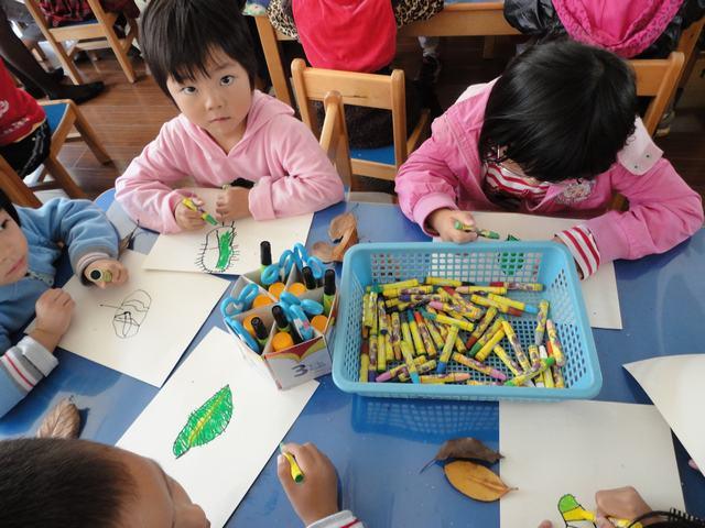 宝贝们尝试绘画树叶只见宝贝们先沿着树叶的周围描下树叶的轮廓,接着
