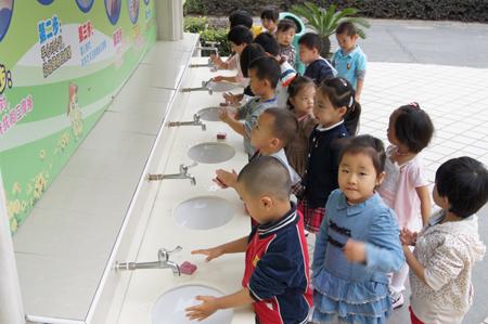 在幼儿洗手池上方悬挂生动形象的洗手步骤图,营造浓厚氛围.