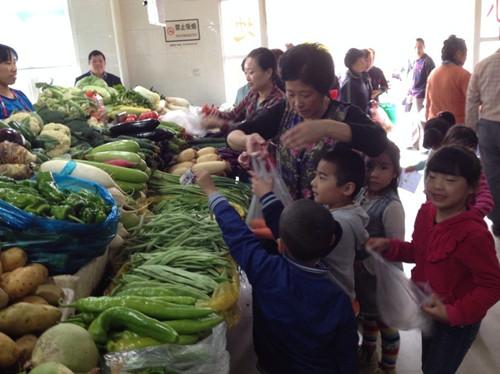 在回幼儿园的路上,孩子们互相聊着今天自己买菜遇到的有趣事,提着