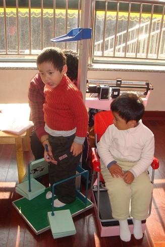 前一个小朋友在检查,后面一个小朋友坐在小椅子上准备好.
